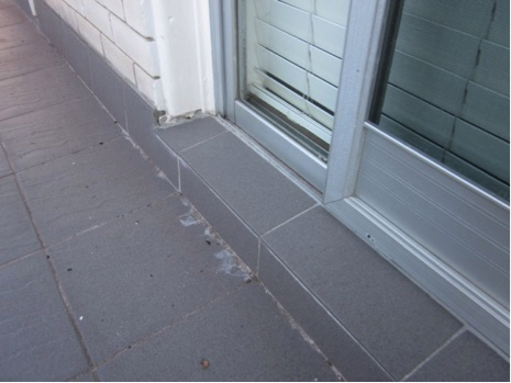 Residential frame with weepholes blocked by sill tiles